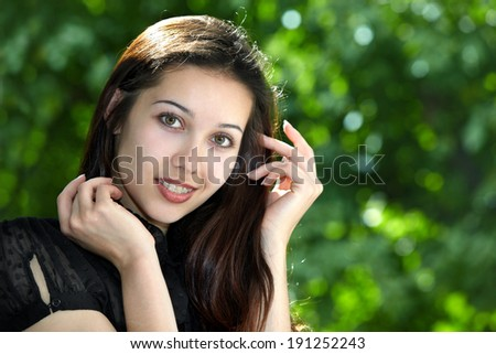 Model girl with braces on a background of trees - stock photo