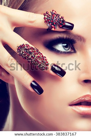 Model  girl  with burgundy manicure  nail and fashion jewelry   rings  . Beauty , fashion and cosmetics - stock photo