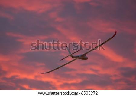 Model glider plane flying at sunset - stock photo