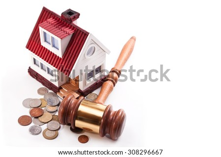 Model homes, money and auction hammer on a white background - stock photo