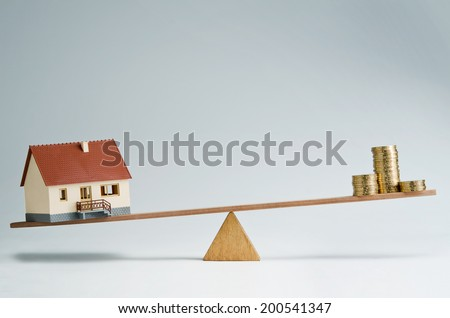 Model house and money coins balancing on a seesaw - stock photo