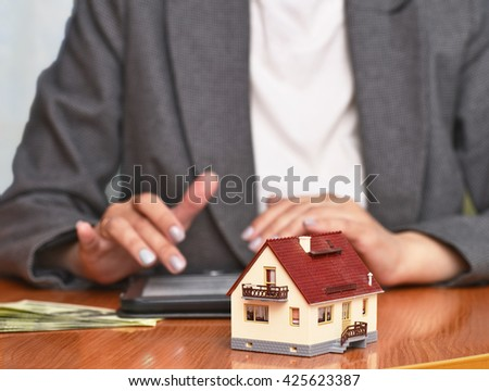 Model house on background woman in a suit, blurry - stock photo