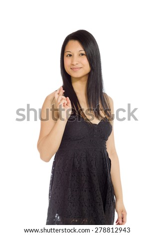 Model isolated on plain background in studio with fingers crossed - stock photo