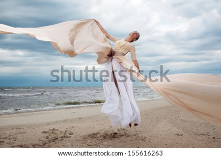 model jumps with long dress like a wings at the beach - stock photo