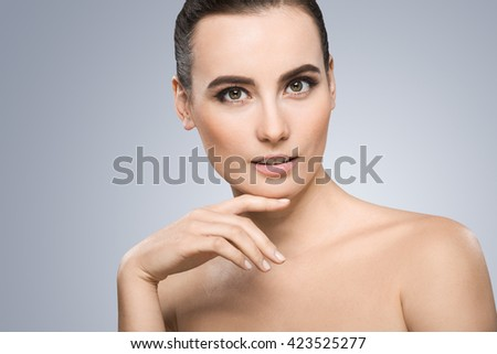 Model looking at camera. Head a little bit aside. Wearing pigtail, nice make-up. Light smile. Fingers touching chin. Beauty portrait, head and shoulders. Indoor, studio - stock photo
