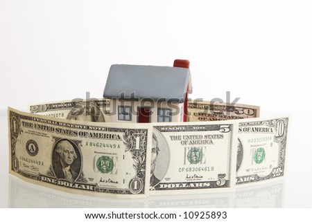 Model of a house behind a fence from dollars - stock photo