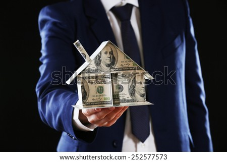 Model of house made of money in male hands on dark background - stock photo