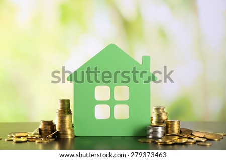 Model of house with coins on wooden table on blurred background - stock photo