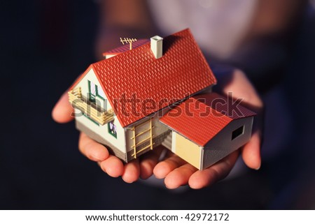 model of house with garage on hands - stock photo