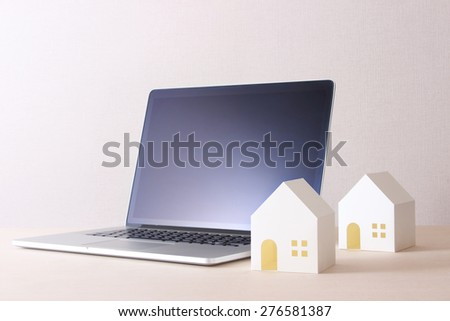 model of the house and a laptop - stock photo