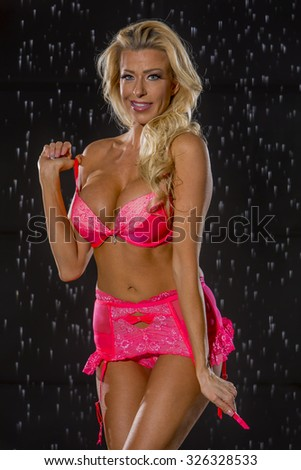 Model posing against a studio rain curtain - stock photo