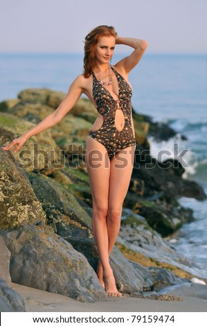 Model posing pretty at rocky beach in designers animal printed swimsuit - stock photo