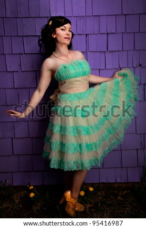 Model wearing a turquoise dress against a purple background - stock photo
