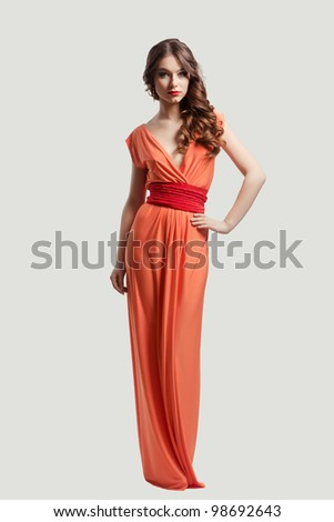 Model with beautiful long hair posing in orange dress isolated - stock photo