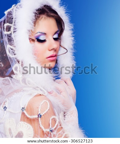 model with bright party makeup against blue background, winter topic - stock photo