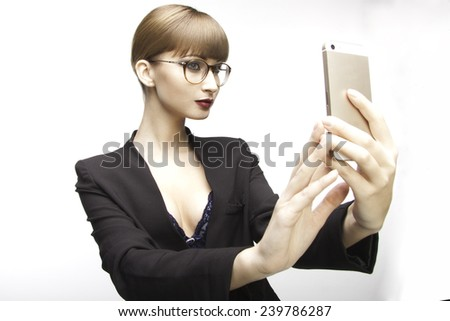 model with glasses and brown forelock  in a black jacket. woman distracted at work. making self photo on her mobile phone - stock photo