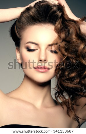 Model with long hair. Waves Curls Hairstyle. Hair Salon. Updo. Fashion model with shiny hair. Woman with healthy hair girl with luxurious haircut. Hair loss Woman with hair volume.  - stock photo