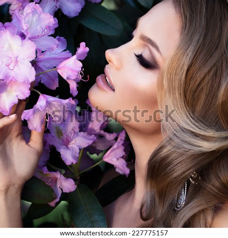 Model with perfect skin takes beautiful flowers in her hands. Summer fairy portrait. Long permed hair. - stock photo