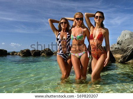 models posing standing in shallow water of tropical ocean - stock photo