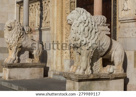 Modena, Cathedral: lion statue and reliefs by Wiligelmus - stock photo