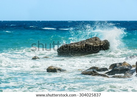 Moderate sea waves hitting the rocks near the beach - stock photo