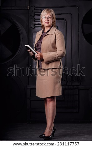 Modern adult business woman standing on a background of space with industrial design. Woman holding a book to record notes about the production processes. Woman engineer by profession or researcher. - stock photo