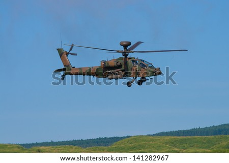 Modern ah-apache military attack helicopter in flight - stock photo