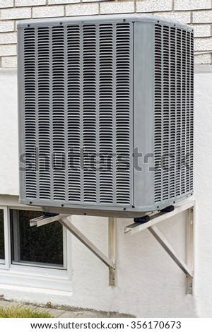 Modern air conditioner unit attach to the brick wall - stock photo