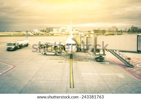 Modern airplane at the terminal gate ready for takeoff - International airport with dramatic sky - Concept of emotional travel around the world on a nostalgic filtered look - stock photo