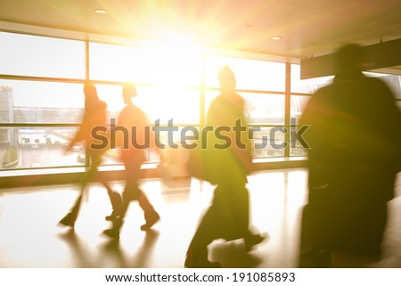 Modern airport passenger aisle interior glass wall of windows in hurry people - stock photo