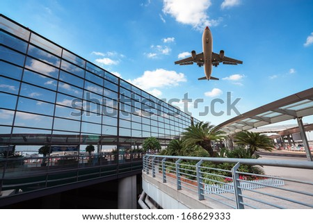 modern airport terminal and aircraft in shanghai against a blue sky  - stock photo