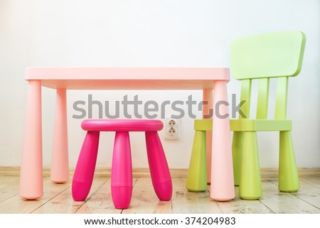 Modern and comfortable soft set of children's furniture, a table, a chair and a stool in the apartment - stock photo