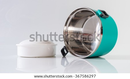 Modern and simplistic greenish blue color lunch box. Isolated on empty background. Slightly de-focused and close-up shot. Copy space. - stock photo