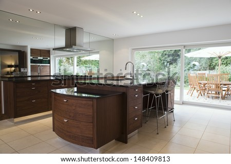 Modern and spacious kitchen with dining area in the porch - stock photo