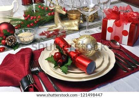 Modern and stylish Christmas dinner table setting including plates, glasses and placemats, bon bons and Christmas decorations Landscape (horizontal) orientation. - stock photo