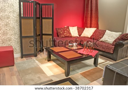 Modern and stylish dining room with sofa and table. Luxurious cushions. Red toned walls and dressing screen. - stock photo
