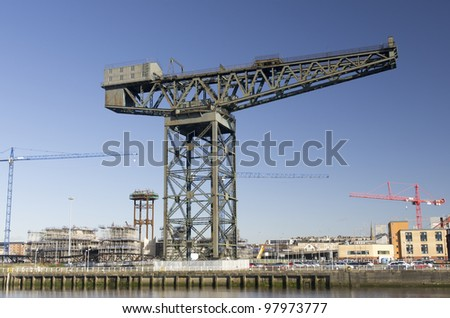 Modern and traditional cranes on the landmark quayside of River Clyde in Glasgow, Scotland - stock photo