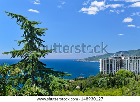 Modern apartment block overlooking a beautful blue bay with lush green tropical vegetation in the foreground - stock photo