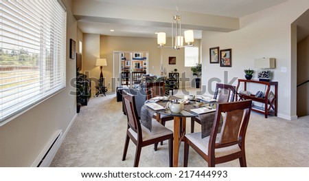 Modern apartment interior with open floor plan. DIning area with served round table and chairs - stock photo
