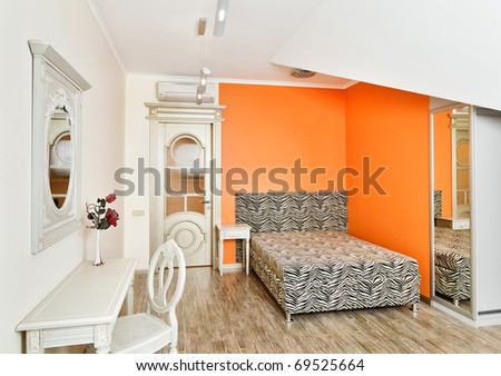 Modern art deco style bedroom in bright orange colors with zebra patterned bed on loft room - stock photo