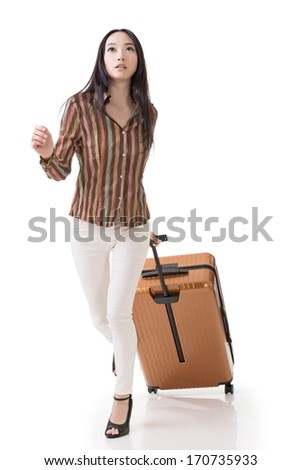 Modern Asian woman running and holding a suitcase, full length portrait isolated on white background. - stock photo
