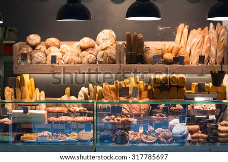 Modern bakery with assortment of bread, cakes and buns  - stock photo