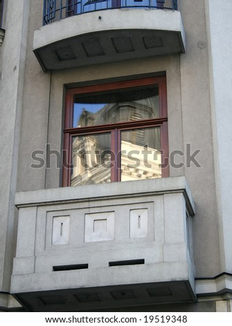 Modern balcony with old building in reflection - stock photo