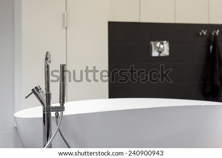 Modern bathroom equipped with oval bath and chrome tap - stock photo