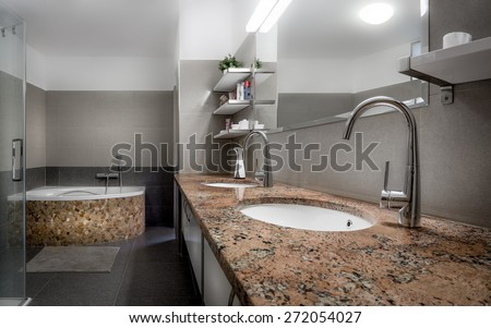 Modern bathroom in cool style with glass shower and bathtub lined with red stones and marble - stock photo