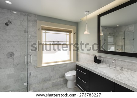 Modern bathroom in white with Marble counter tops and all new appliances including glass shower. - stock photo