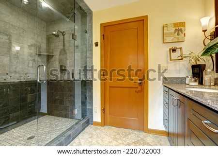 Modern bathroom interior with glass door shower and tile wall trim. Bathroom with bright orange door - stock photo