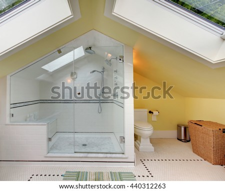 Modern bathroom upstairs with large shower, toilet and vaulted ceiling.  - stock photo
