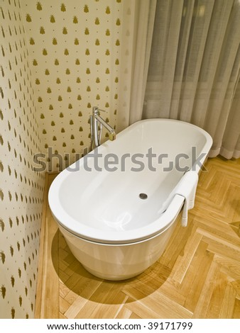 Modern bathroom with a bathtub, wooden flooring and wallpaper with bee motif - stock photo