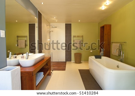 Modern bathroom with pastel coloured walls and white bath. There's also a wood floored open shower - stock photo